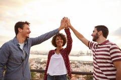 Handeln mit drei glückliches Freunden hohen fünf lizenzfreie stockbilder