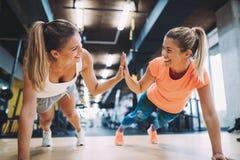 Handeln mit zwei drückt das sportliche Mädchen ups in Turnhalle stockfoto