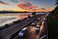 Handeln Sie bei Sonnenuntergang, die Scheinwerfer, die herauf die Straße beleuchten stockfotos