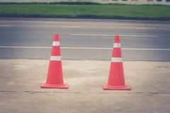 Handeln Sie den Kegel, der auf konkretem Boden am Parkplatz neben Straße steht Lizenzfreie Stockbilder