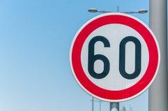 Handeln Sie Höchstgeschwindigkeitszeichen für Beschränkung auf 60 Kilometern oder Meilen pro Stunde mit Hintergrund des blauen Hi Stockfoto