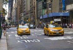 Handeln Sie in New York City mit den berühmten gelb-farbigen Taxis, die vorbei überschreiten Lizenzfreies Stockbild