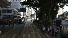 Handeln Sie Straße mit Retro- Tram und chinesischem Volk Wegüberfahrtstraße bei Wan Chai stock video footage