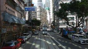 Handeln Sie Straße mit Retro- Tram und chinesischem Volk Wegüberfahrtstraße bei Wan Chai stock video