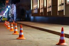 Handeln Sie warnenden Kegel in der Reihe auf Straße, um Platz für Parkplatz zu trennen Stockbild