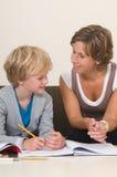 Handeln von Heimarbeit mit Mutter lizenzfreies stockfoto
