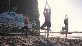 Handeln Yogaübungen - ein junger Mann, der die Haltung und die jungen Frauen zeigt, wiederholt sie stock video