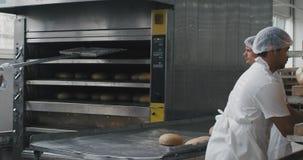 Handelscharismatischer Bäcker der backwarenindustrie und seine Berufsunterstützung entfernen das gekochte Brot von der Ofenmaschi stock video