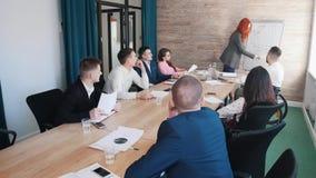 Handelsconferentie Een vrouw trekt de grafieken op de raad stock afbeeldingen