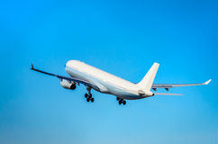 Handelsflugzeug, das in den blauen Himmel sich entfernt Lizenzfreie Stockfotografie