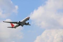 Handelsflugzeug, das oben in blauen Himmel fliegt Stockbild