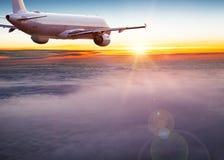 Handelsflugzeugfliegen über drastischen Wolken lizenzfreie stockbilder
