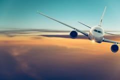 Handelsflugzeugfliegen über drastischen Wolken lizenzfreie stockfotografie