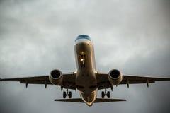 Handelsflugzeugfliegen unter drastischen Wolken lizenzfreie stockfotografie