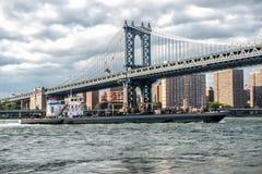Handelsfrachterschiff in Eat Fluss in New York City unter Manhattan-Brücke lizenzfreie stockfotografie