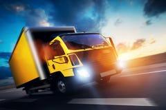 Handelsfrachtlieferwagen mit dem Anhänger, der auf Landstraße bei Sonnenuntergang fährt Stockbilder