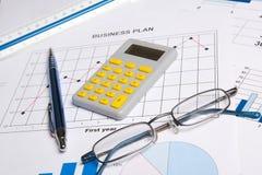 Handelspapieren met grafieken, grafieken, glazen, pen en calculator stock foto's