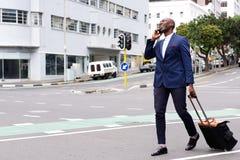 Handelsreiziger die en op mobiele telefoon lopen spreken stock fotografie