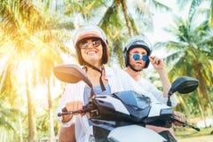 Handelsresande för Ð-¡ ouple som rider mopedsparkcykeln i säkerhetshjälmar under tropisk semester under palmträd royaltyfri bild