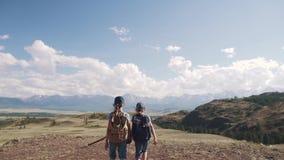 Handelsresande för två små flickor som går bergen som rymmer händer barn av turister som promenerar banan mot stock video