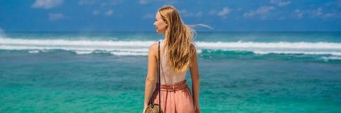 Handelsresande för ung kvinna på att förbluffa den Melasti stranden med turkosvatten, Bali öIndonesien BANER, LÅNGT FORMAT fotografering för bildbyråer