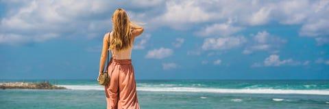 Handelsresande för ung kvinna på att förbluffa den Melasti stranden med turkosvatten, Bali öIndonesien BANER, LÅNGT FORMAT royaltyfri foto