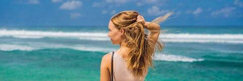 Handelsresande för ung kvinna på att förbluffa den Melasti stranden med turkosvatten, Bali öIndonesien BANER, LÅNGT FORMAT royaltyfri fotografi