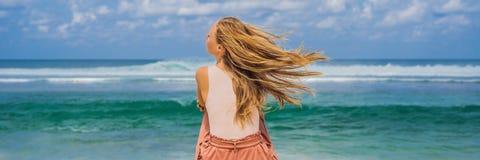Handelsresande för ung kvinna på att förbluffa den Melasti stranden med turkosvatten, Bali öIndonesien BANER, LÅNGT FORMAT arkivbilder