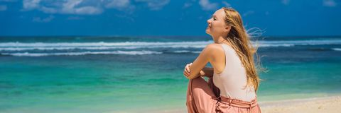 Handelsresande för ung kvinna på att förbluffa den Melasti stranden med turkosvatten, Bali öIndonesien BANER, LÅNGT FORMAT royaltyfri bild