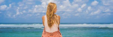 Handelsresande för ung kvinna på att förbluffa den Melasti stranden med turkosvatten, Bali öIndonesien BANER, LÅNGT FORMAT royaltyfria foton