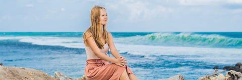 Handelsresande för ung kvinna på att förbluffa den Melasti stranden med turkosvatten, Bali öIndonesien BANER, LÅNGT FORMAT arkivfoto