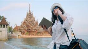 Handelsresande för ung kvinna som använder den läs- resehandboken app som för digital minnestavladator söker information stock video