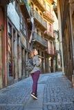 Handelsresande för ung kvinna som går till och med de gamla gatorna av staden i Porto, Portugal royaltyfri bild