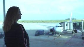 Handelsresande för ung kvinna som ser till fönstret, medan vänta flygplanet i avvikelsevardagsrum i flygplats härligt se för flic arkivfilmer