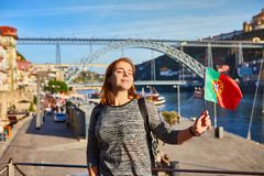 Handelsresande för ung kvinna som tillbaka står med den portugisiska flaggan som tycker om härlig cityscapesikt på den Douro flod fotografering för bildbyråer