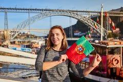 Handelsresande för ung kvinna som tillbaka står med den portugisiska flaggan som tycker om härlig cityscapesikt på den Douro flod arkivfoto