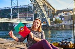 Handelsresande för ung kvinna som tillbaka står med den portugisiska flaggan som tycker om härlig cityscapesikt på den Douro flod arkivbilder