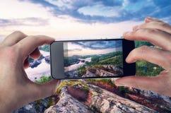 Handelsresande fotograferad bergflod på en smartphone Royaltyfria Bilder