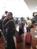 Handelsresande med deras bagage på flygplatsen Arkivfoto