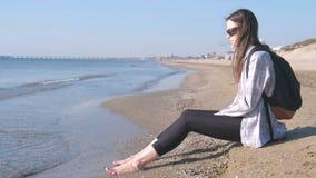 Handelsresande med en ryggsäck som sitter på en sandig strand och ser havet sätta på land flickabarn arkivfilmer