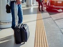 Handelsresande med resväskan på plattformen i flygplatsterminal royaltyfri foto