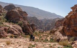 Handelsresande med ryggsäcken som fotvandrar i Petra den rosa staden i Jordanien, Mellanösten lopplivsstil och äventyrligt begrep arkivfoton