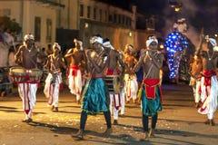 Handelsresande och flöjtspelare utför framåt av en ståtaelefant under Esalaen Perahera i Kandy, Sri Lanka Arkivfoton