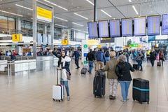 Handelsresande och kvinna med sjaletten på den holländareSchiphol flygplatsen royaltyfria bilder