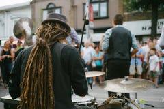 Handelsresande och musikband som utför levande musik på en gata arkivbilder