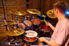 Handelsresande Playing Drum Kit In Studio royaltyfri fotografi