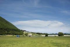 Handelsresande som folket bygger tältet som campar på gräsfältet för, vilar och sover nära berget Fotografering för Bildbyråer