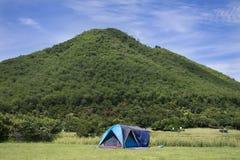 Handelsresande som folket bygger tältet som campar på gräsfältet för, vilar och sover nära berget Arkivbild
