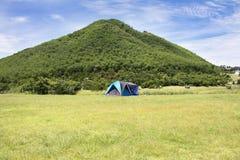 Handelsresande som folket bygger tältet som campar på gräsfältet för, vilar och sover nära berget Royaltyfria Foton