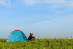 Handelsresande som har att campa med ett tält på gräsfält arkivfoton